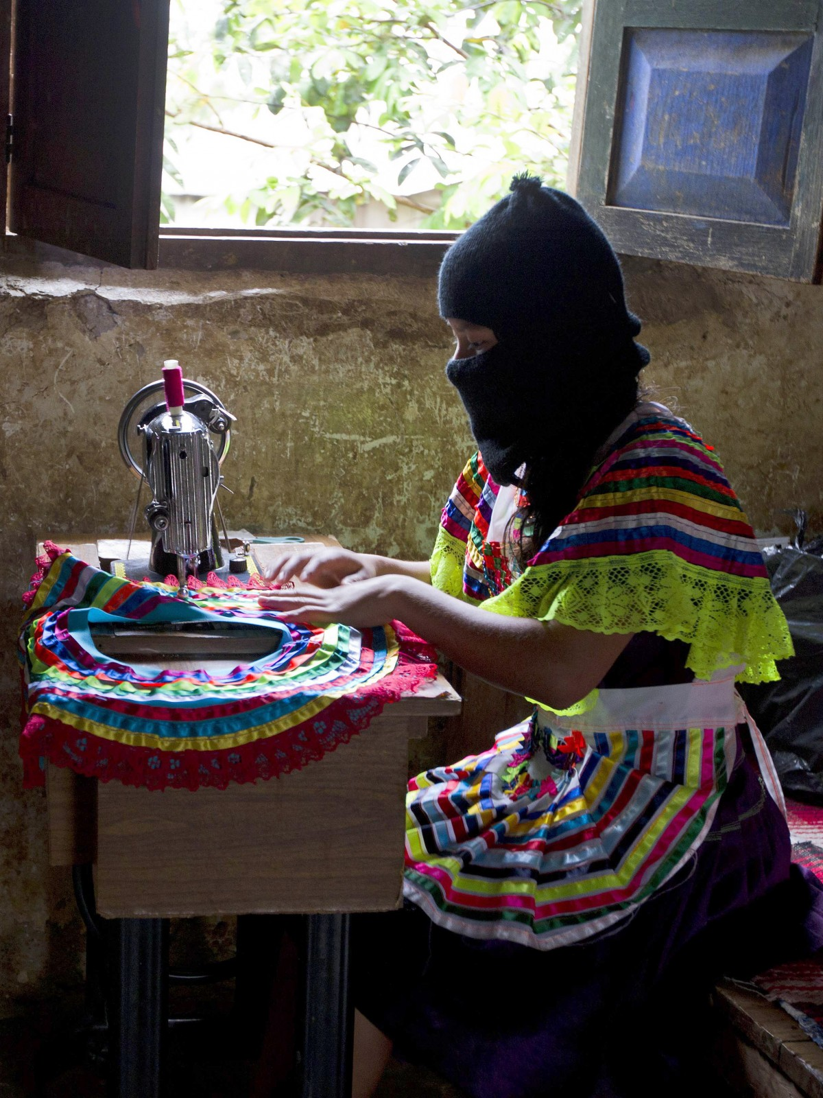 In this Dec. 27, 2013 photo, a woman sews part of a traditional skirt in the Zapatista controlled community of La Garrucha, Mexico. Since their uprising 20 years ago, Zapatistas, known by their initials as the EZLN, have lived in secretive, closed-off enclaves they have formed in the half-dozen communities they hold. But in the last five months the rebels have opened up their communities to more than 7,000 Mexicans and foreigners interested in learning about how they self-govern and maintain their independence and way of life. Those invited stayed for a week at a time and lived with a Zapatista family. Members of these communities wear masks to hide their identities when outsiders, interested in learning about how they self-govern and maintain their way of life, gain access to visit them. (AP Photo/Christian Palma)