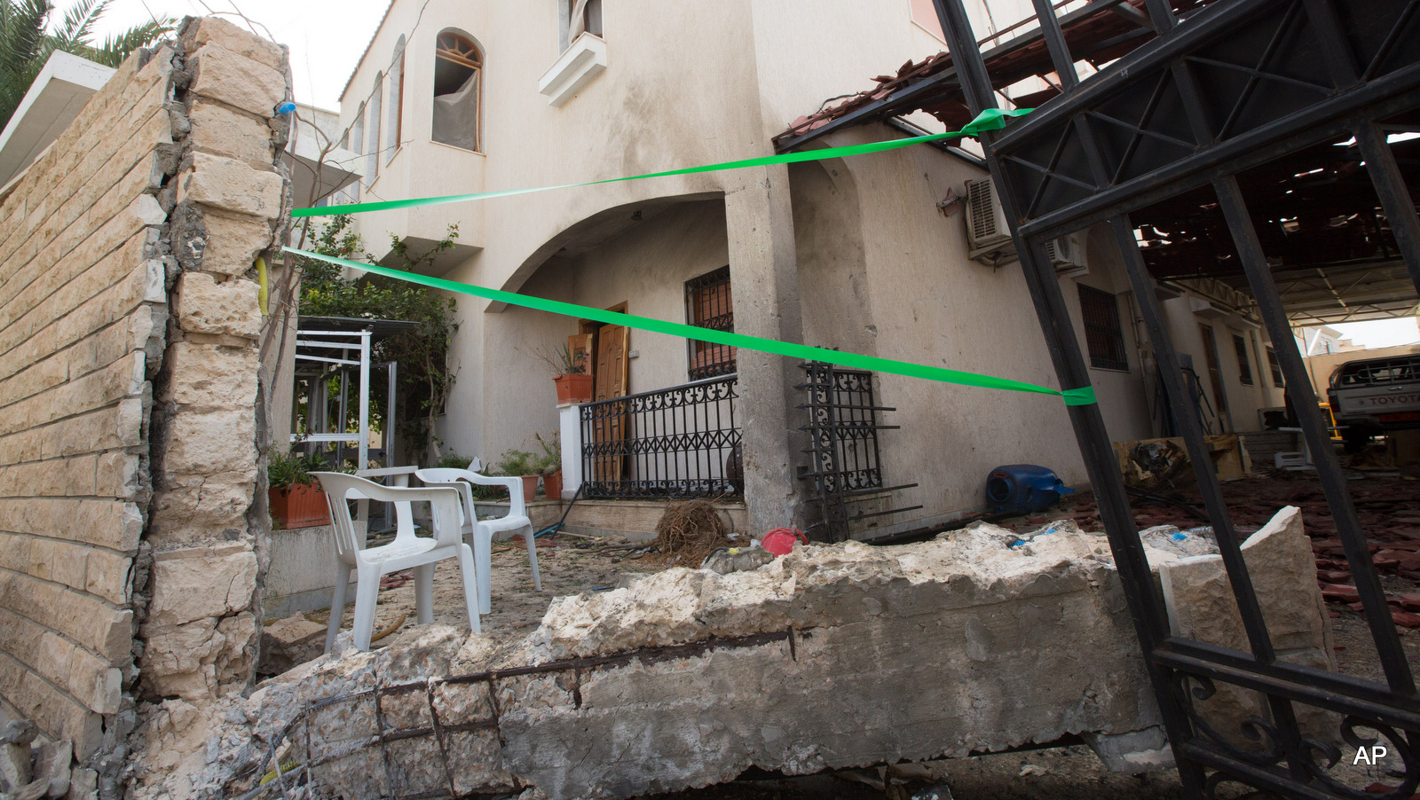 Police tape secures the Iranian ambassador's house after it received minor damage from an improvised explosive device placed among garbage bags, in Libya's capital, Tripoli, Libya, Sunday, Feb. 22, 2015.