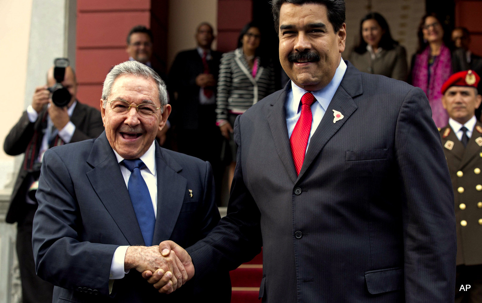 Cuba's President Raul Castro, left, shakes hands with Venezuela's President Nicolas Maduro in front of the press after arriving to Miraflores presidential palace for an emergency ALBA meeting in Caracas, Venezuela, Tuesday, March 17, 2015.