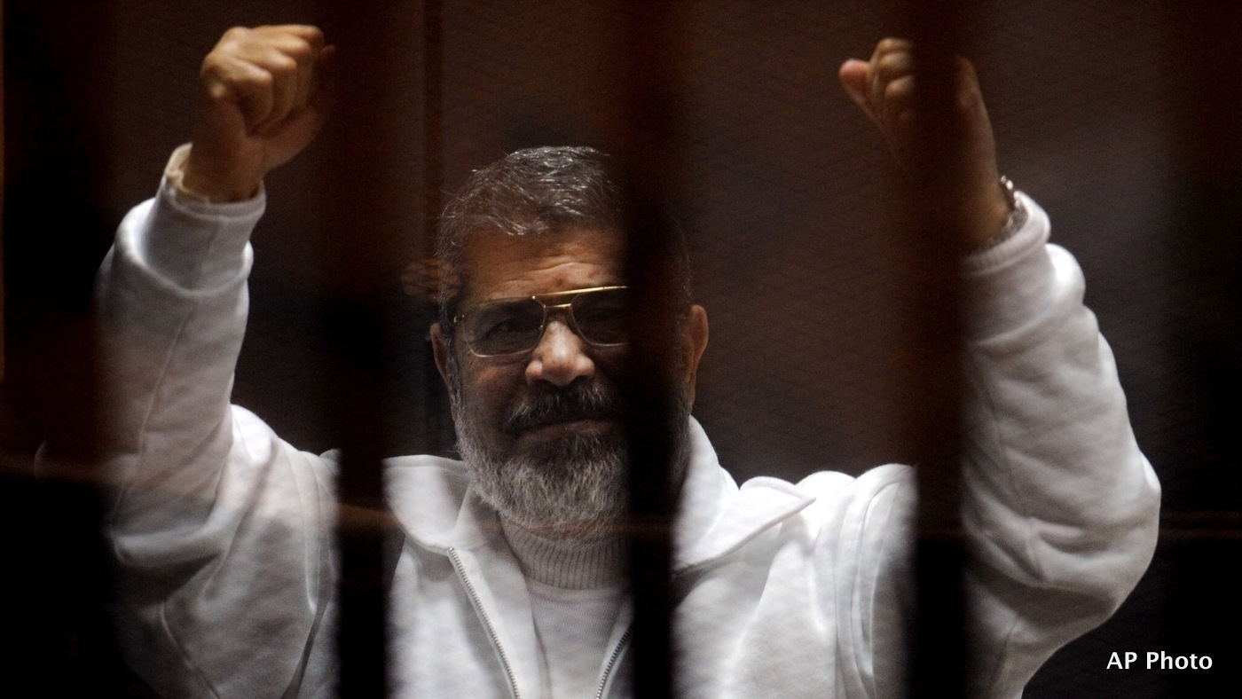 Egypt's ousted President Mohammed Morsi gestures in a defendant cage during his hearing at a courtroom in Cairo, Egypt, Tuesday, March 3, 2015. (AP Photo/Ahmed Omar)