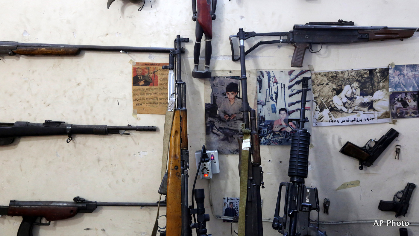 This Wednesday, Feb. 25, 2015 photo shows, photos of gunsmith Bahktiyar Sadr-Aldeen as a child, center, and his father, right, hung on a wall at his gun shop, in Irbil, northern Iraq. Sadr-Aldeen, an Iraqi Kurd, has seen his business shoot up by 50 percent since last June, when the Islamic State took over the Iraqi city of Mosul.
