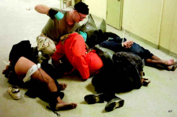 Cpl. Charles A. Graner Jr. appearing to punch one of several handcuffed detainees lying on the floor in late 2003 at the Abu Ghraib prison in Baghdad, Iraq. (AP Photo)
