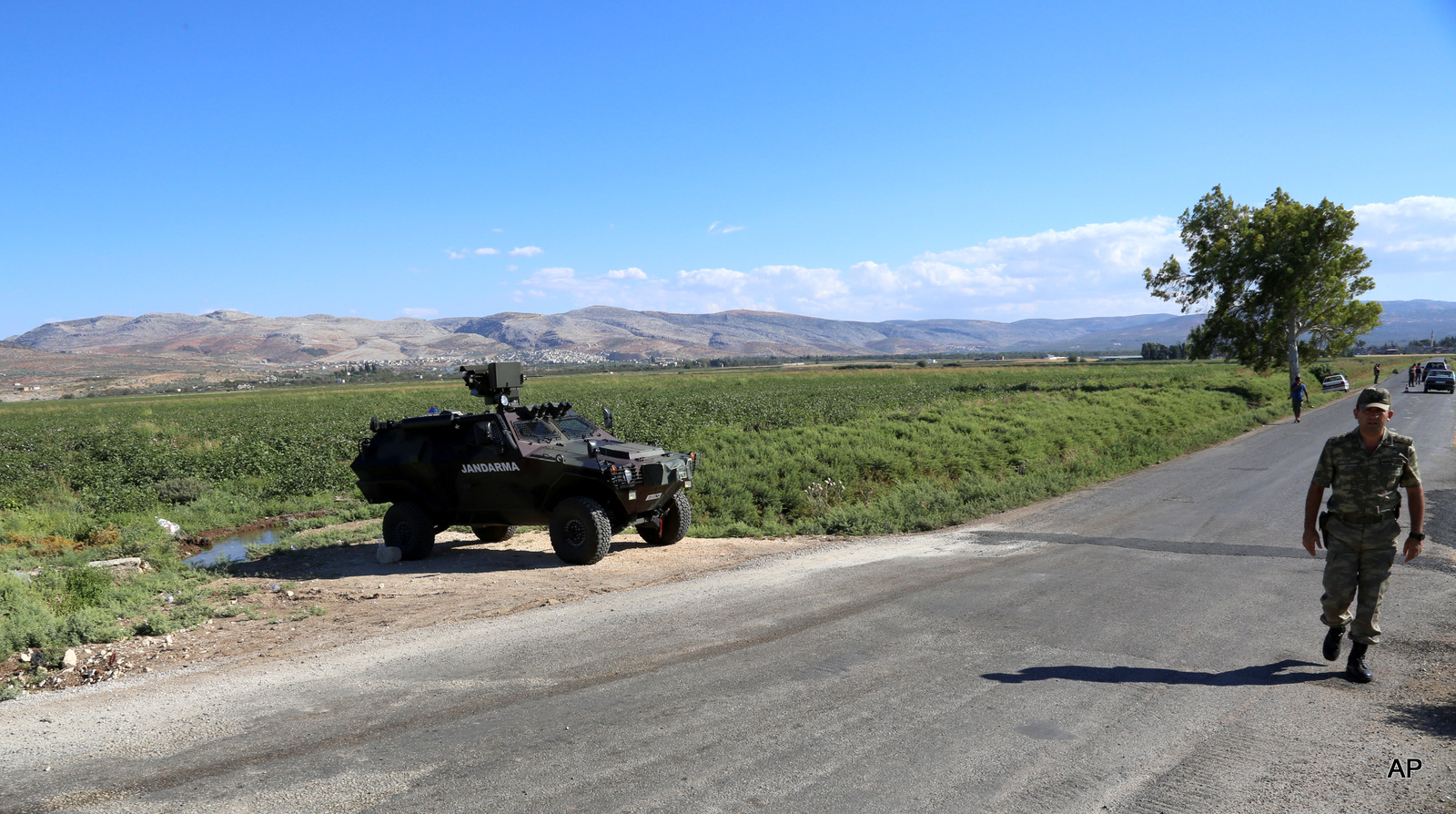 Turkish soldiers patrol a road near Hacipasa, Hatay, Turkey. At the peak of Turkey's oil smuggling boom, the main transit point was a dusty hamlet called Hacipasa on the Orontes River that marks the border with Syria, Saturday, Sept. 20, 2014. Hacipasa has been a smuggling haven for decades, authorities and residents say. The fuel had come from oil wells in Iraq or Syria controlled by militants, including the Islamic State group, and was sold to middle men who smuggled it across the Turkish-Syrian border.