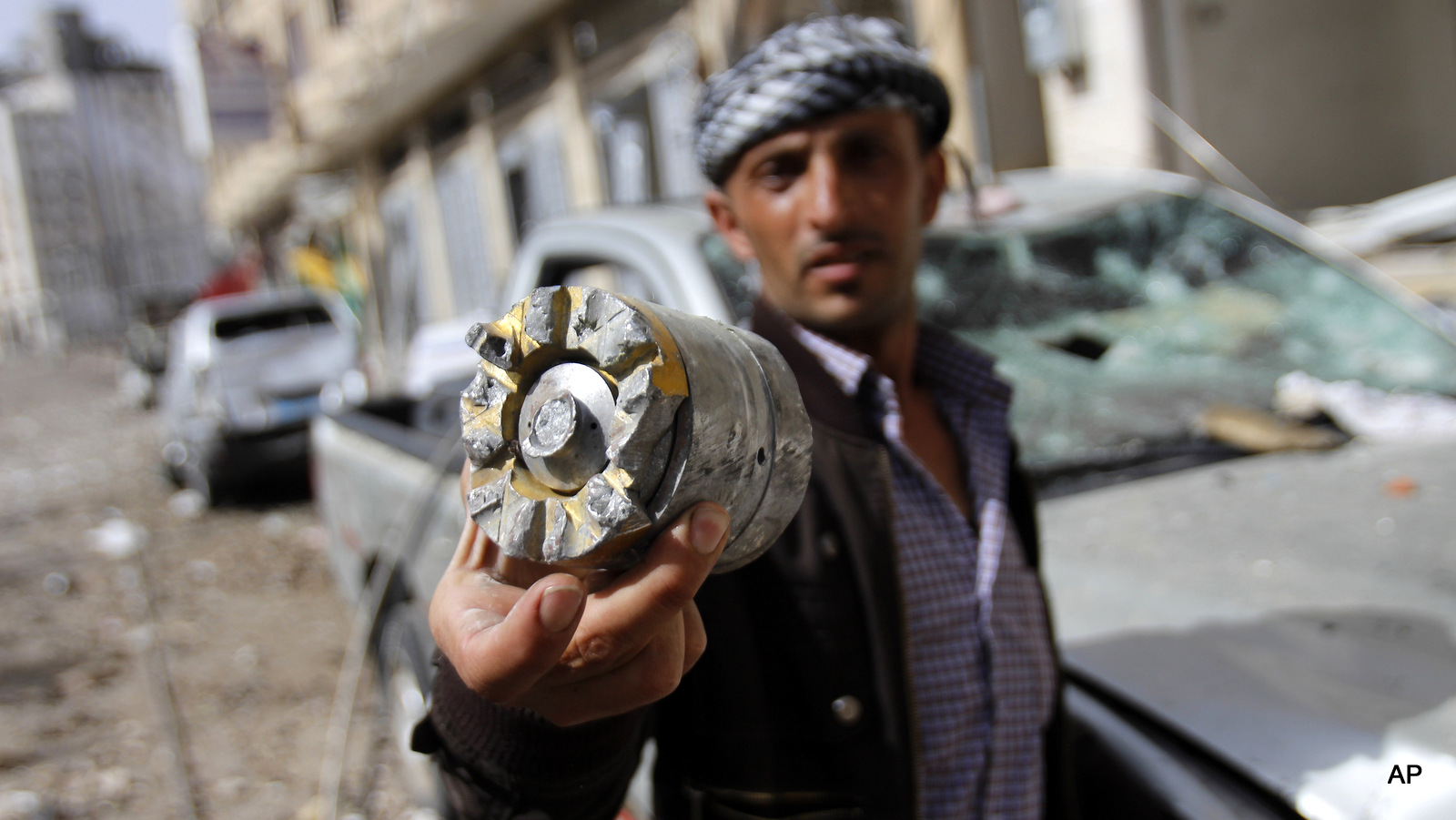 A man holds a cluster comb fragment after a Saudi-led airstrike in Yemen's capital, Monday, April 20, 2015. (AP Photo/Hani Mohammed)