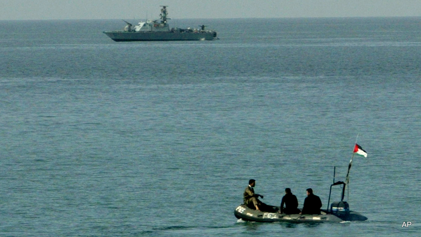 Palestinian police officers sit in a small boat as they pass near an Israeli naval vessel