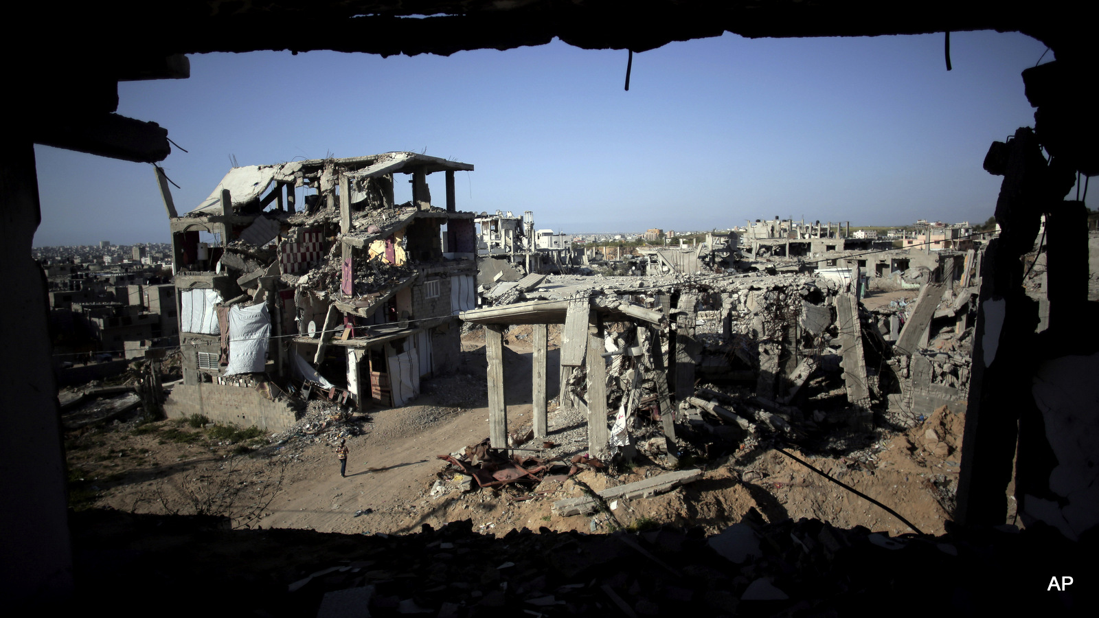 a Palestinian girl walks next to destroyed houses, in the Shijaiyah neighborhood of Gaza City