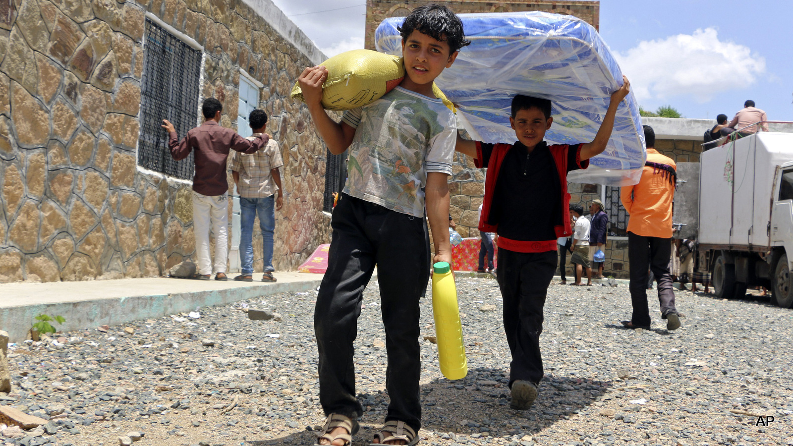 Boys carry relief supplies to their families who fled fighting in the southern city of Aden, during a food distribution effort by Yemeni volunteers, in Taiz, Yemen.