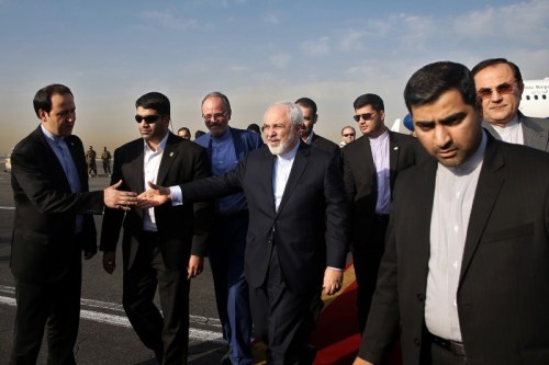 Iran's Foreign Minister Mohammad Javad Zarif, who is also Iran's top nuclear negotiator, center, shakes hands with an official upon arrival at the Mehrabad airport in Tehran, Iran, Wednesday, July 15, 2015. Zarif and his entourage returned to Tehran on Wednesday morning, a day after Iran and the West reached a historic nuclear deal. (AP Photo/Ebrahim Noroozi)