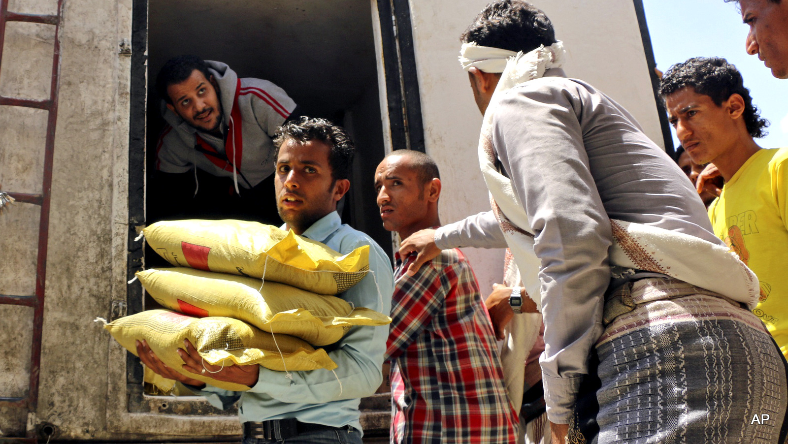 A Yemeni volunteer carries bags of rice to displaced people
