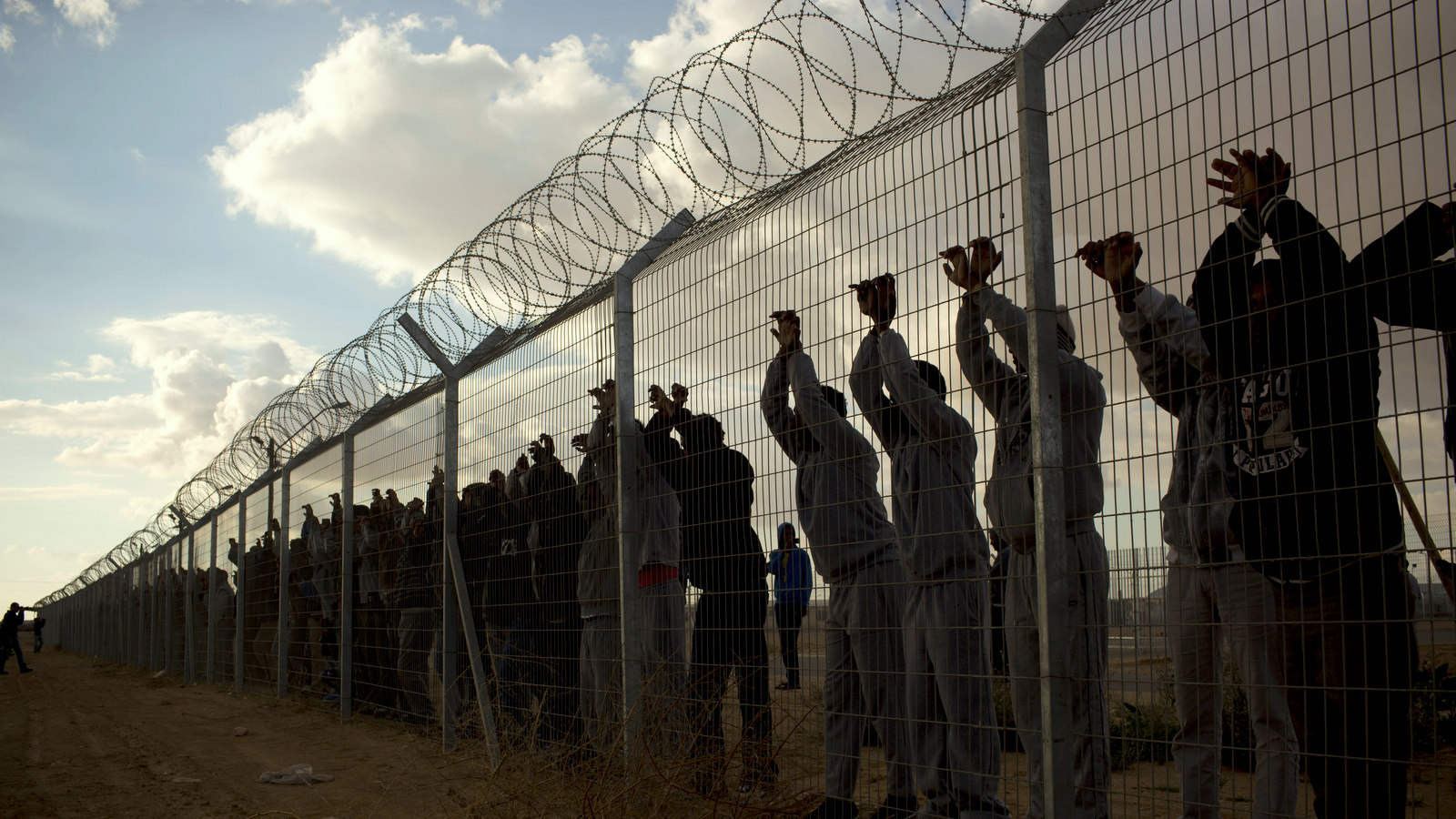 African migrants stands inside Holot detention center as others protest outside against the detention center near Ktsiot the Negev Desert in southern Israel, Monday, Feb. 17, 2014. (AP Photo/Oded Balilty)