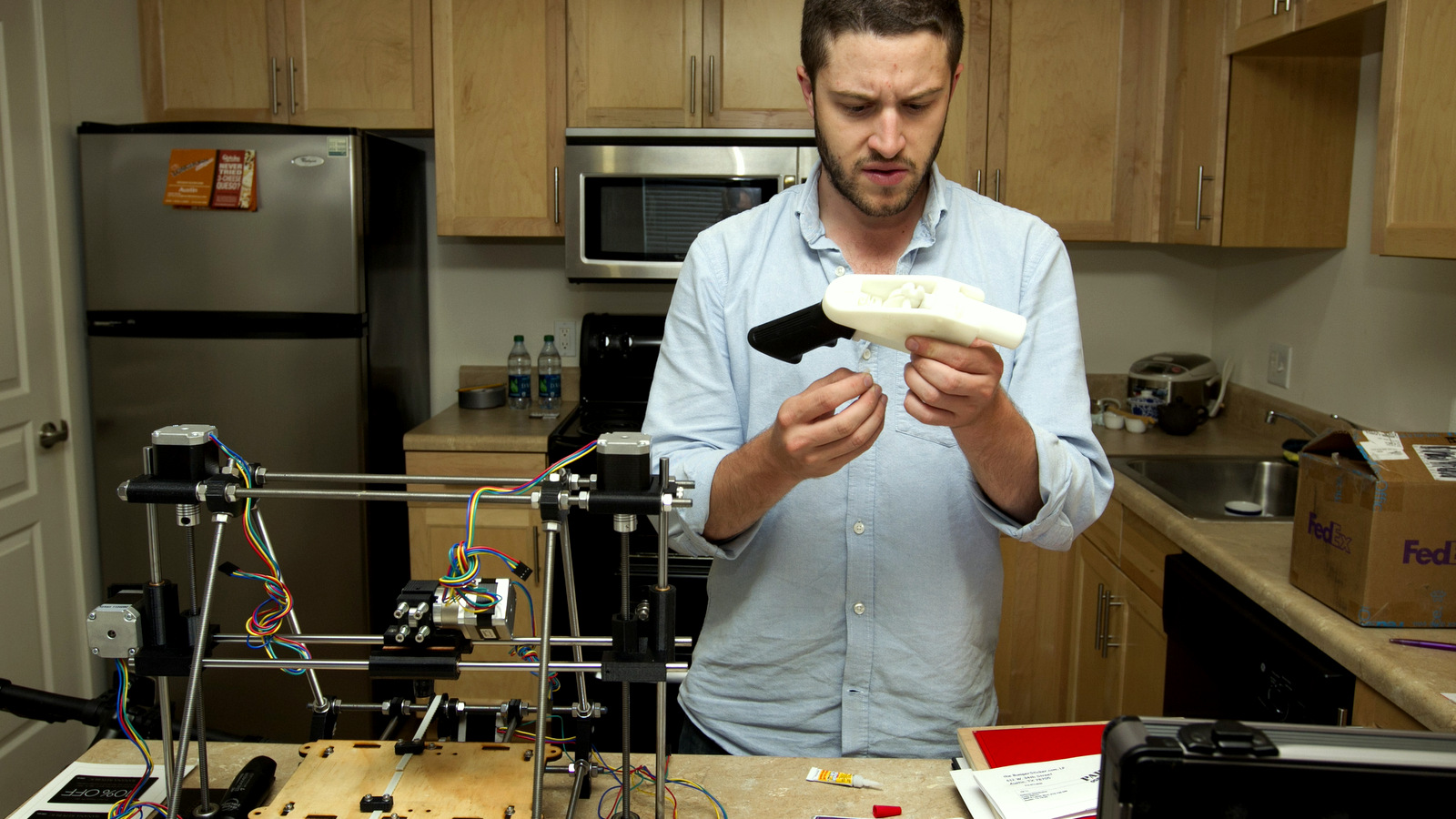 Cody Wilson works on the first completely 3D-printed handgun, The Liberator, at his home in Austin on Friday May 10, 2013. (AP Photo/Austin American Statesman, Jay Janner)