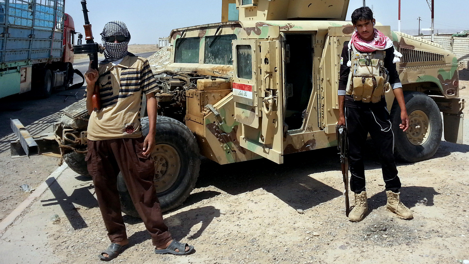 ISIS militants stand with a captured American Humvee, given to the Iraqi Army and captured by ISIS, June 19, 2014. (AP Photo)