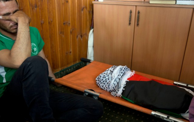 A man mourns alongside the body of a one-and-a-half year old boy, Ali Dawabsheh, during his funeral in Duma village near the West Bank city of Nablus. The sleeping toddler was burned to death when Jewish assailants set fire to two Palestinian homes, an attack that also critically wounded the child's 4-year-old brother and parents. (AP Photo/Majdi Mohammed)
