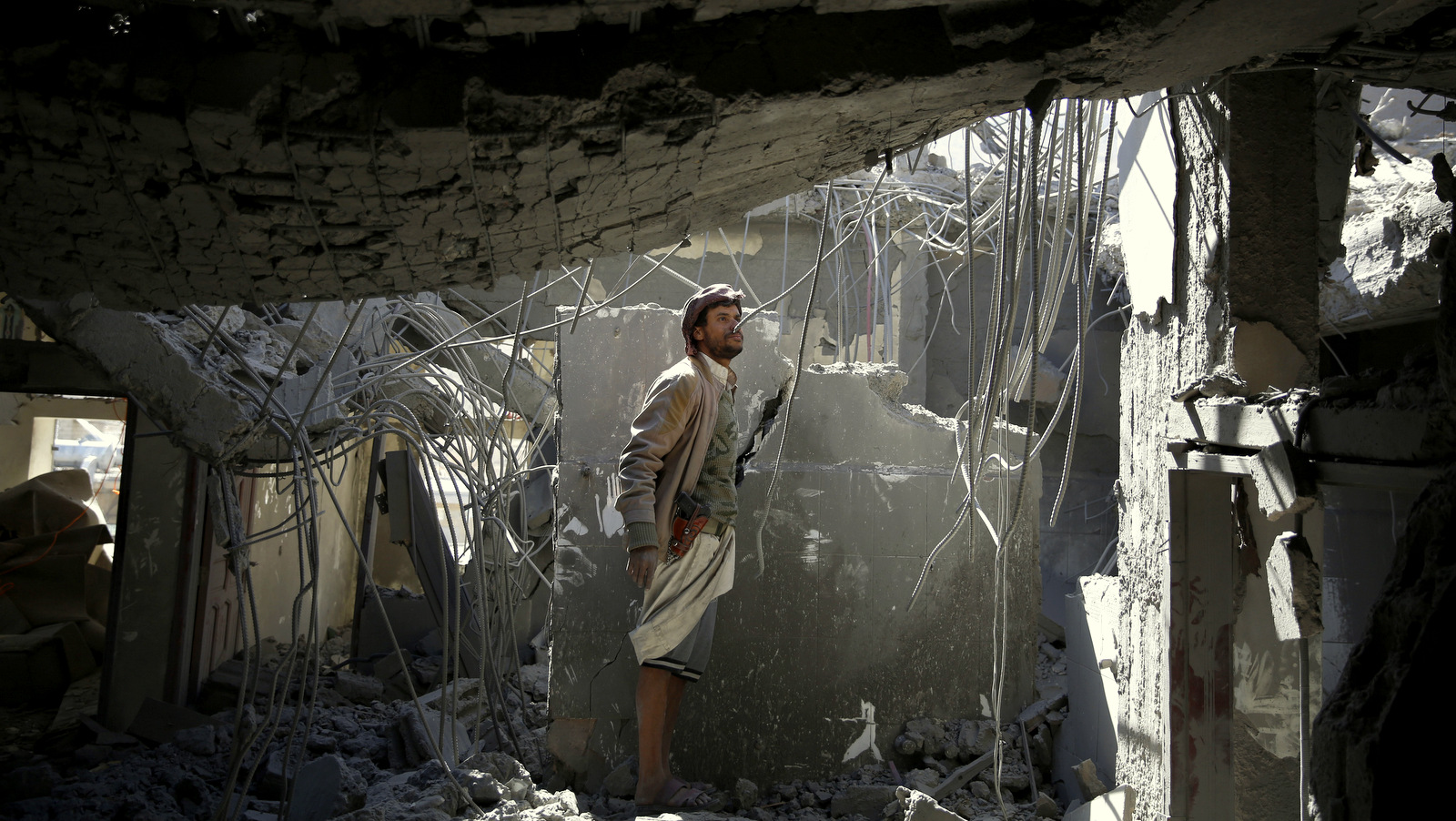 A man inspects his home destroyed by Saudi-led airstrikes in Sanaa, Yemen, Monday, Jan. 4, 2016. According to U.N. figures, the war in Yemen has killed at least 5,884 people since March, when fighting escalated after the Saudi-led coalition began launching airstrikes claiming to be targeting the Houthi rebels. (AP Photo/Hani Mohammed)