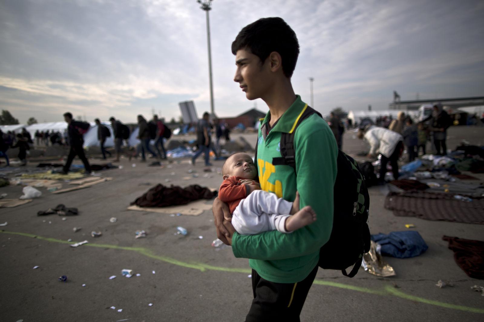 Afghan refugee Rasoul Nazari, 15, holds his 10-month-old nephew Imran after crossing the border between Hungary and Austria in Nickelsdorf, Austria. (AP Photo/Muhammed Muheisen)