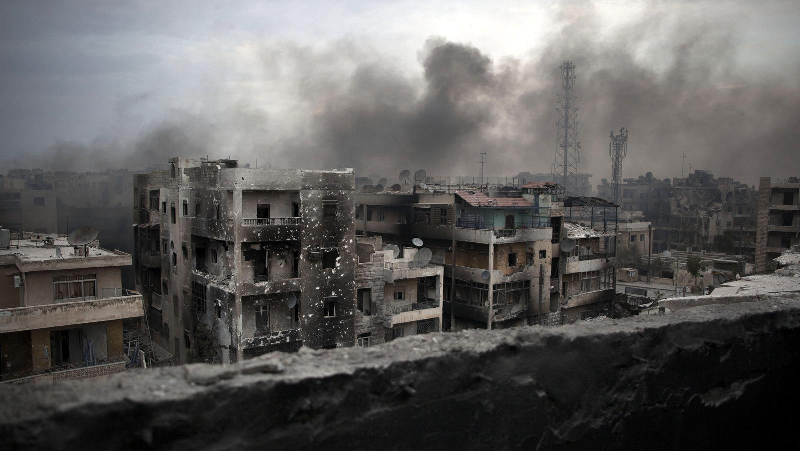 Smoke rises over a battle-scarred Saif Al Dawla district in Aleppo, Syria, on October 2, 2012