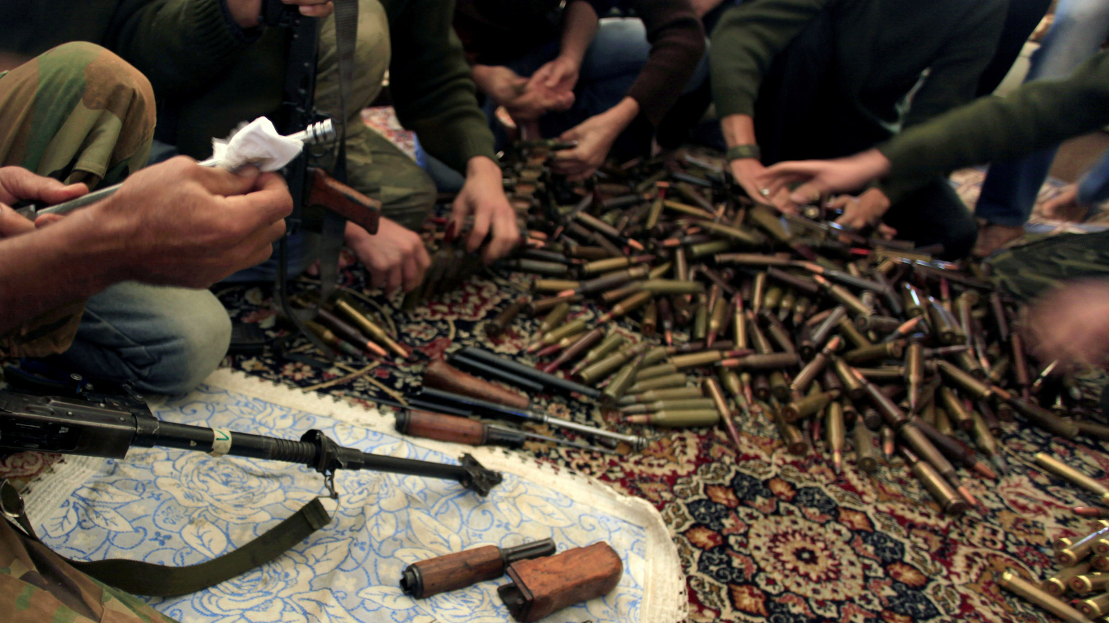 Free Syrian Army fighters clean their weapons and check ammunition at their base on the outskirts of Aleppo, Syria. (Khalil Hamra/AP)