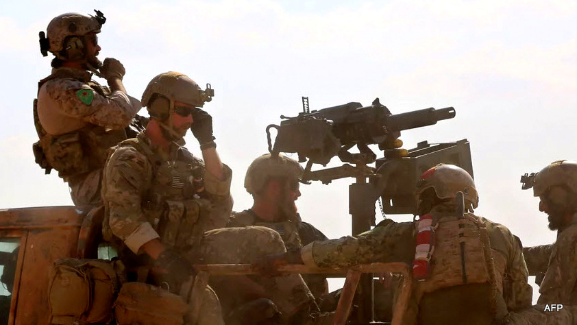 Armed men in uniform identified by Syrian Democratic forces as US special operations forces ride in the back of a pickup truck in the village of Fatisah in the northern Syrian province of Raqa, May 25, 2016.