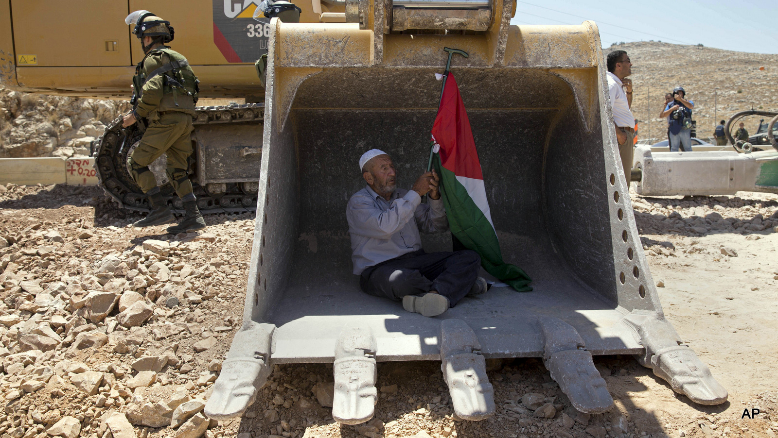 A Palestinian man tries to stop work by an Israeli bulldozer during a protest outside the village of Deir Qaddis, near the West Bank city of Ramallah, Wednesday, July 13, 2016. Dozens of Palestinians demonstrated Wednesday in front of Israeli bulldozers that were bulldozing land outside Deir Qaddis village near Ramallah for an apparent plan to expand a nearby Jewish settlement. The protesters forced the bulldozers to stop, but residents said they resumed work after the protesters left the area.