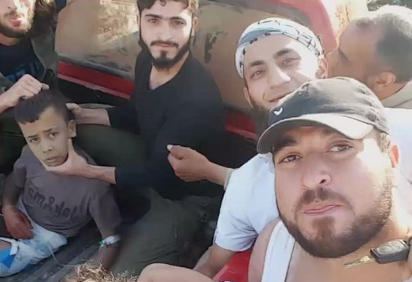 US backed Al-Zenki Syriab rebels display a captured 10 year-old boy shortly before he is decapitated.