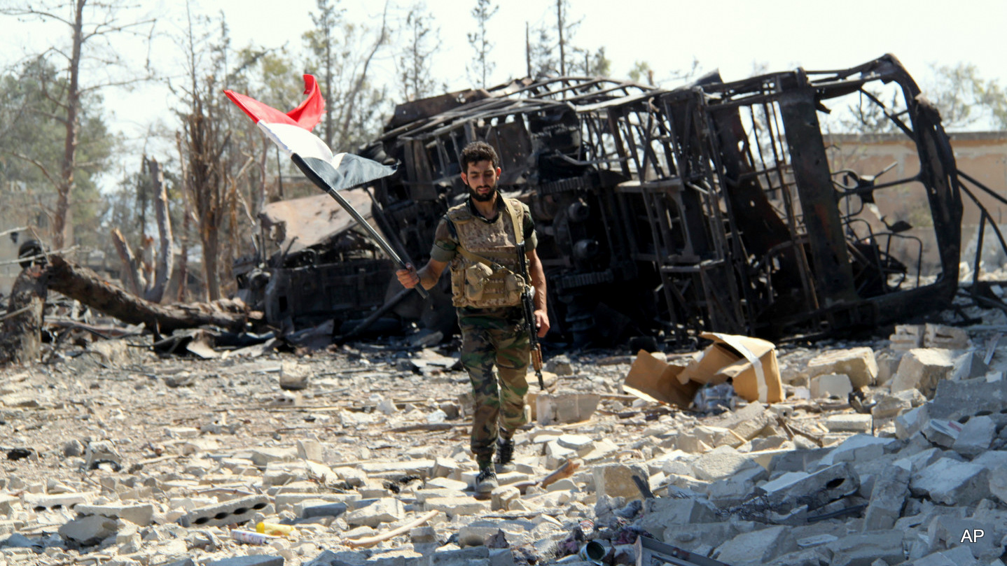 A Syrian soldier carries Syria's national flag after successfully routing rebels from the Aleppo Military Academy in Aleppo, Syria. Sept. 05, 2016.