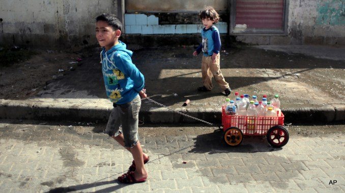 In this Saturday, April 16, 2016 photo, A Palestinian boy uses a homemade wagon made from a plastic crate to wheel bottles full of drinking water in front of a water supply station in Khan Younis refugee camp, southern Gaza Strip. Poor sewage treatment is a feature of life in Gaza, a result of infrastructure damaged during Israel's bombing campaigns and ongoing blockade.