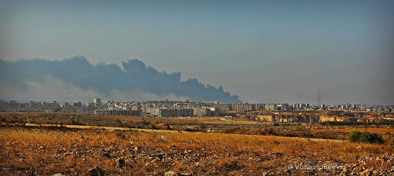 The first view of al-Ramouseh, a suburb in southeastern Aleppo. The smoke is from a burning tarwell after being bombed by terrorists three or four days prior. (Photo by Vanessa Beeley)