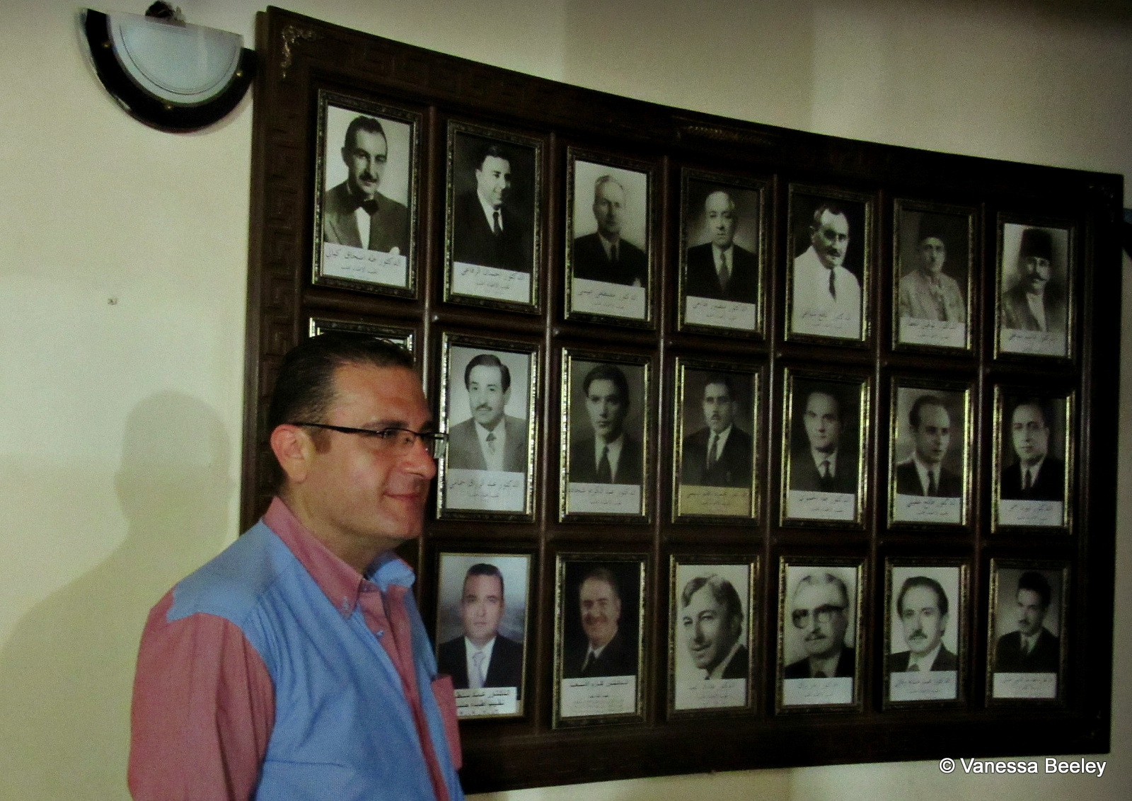 Dr. Zahar Buttal, director of the Aleppo Medical Association, standing next to photos of previous directors at the Aleppo Medical Association building. (Photo by Vanessa Beeley)