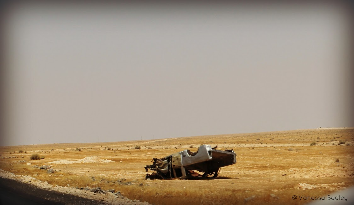 An overturned vehicle bakes in the scorching desert sun on the road to Aleppo. (Photo by Vanessa Beeley.)