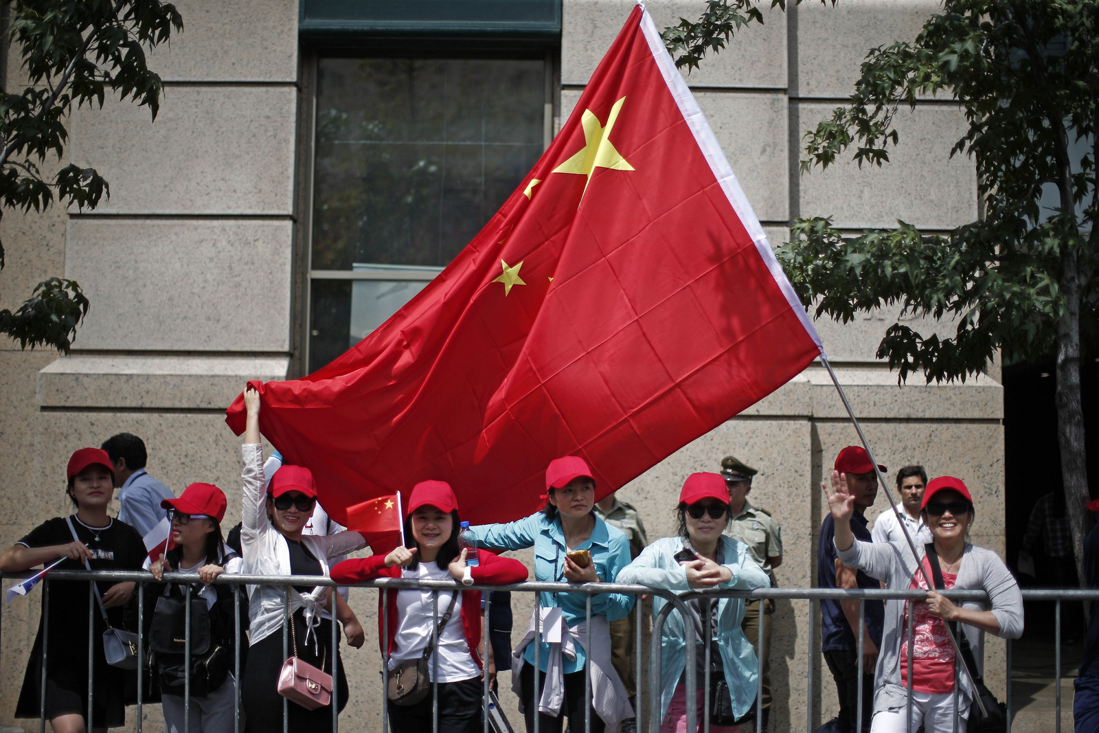 Members of the Chinese community living in Chile await the arrival of China's President Xi Jinping outside La Moneda presidential palace in Santiago, Chile, Tuesday, Nov. 22, 2016. Jinping is in Chile after attending the APEC summit in Peru. (AP Photo/Luis Hidalgo)