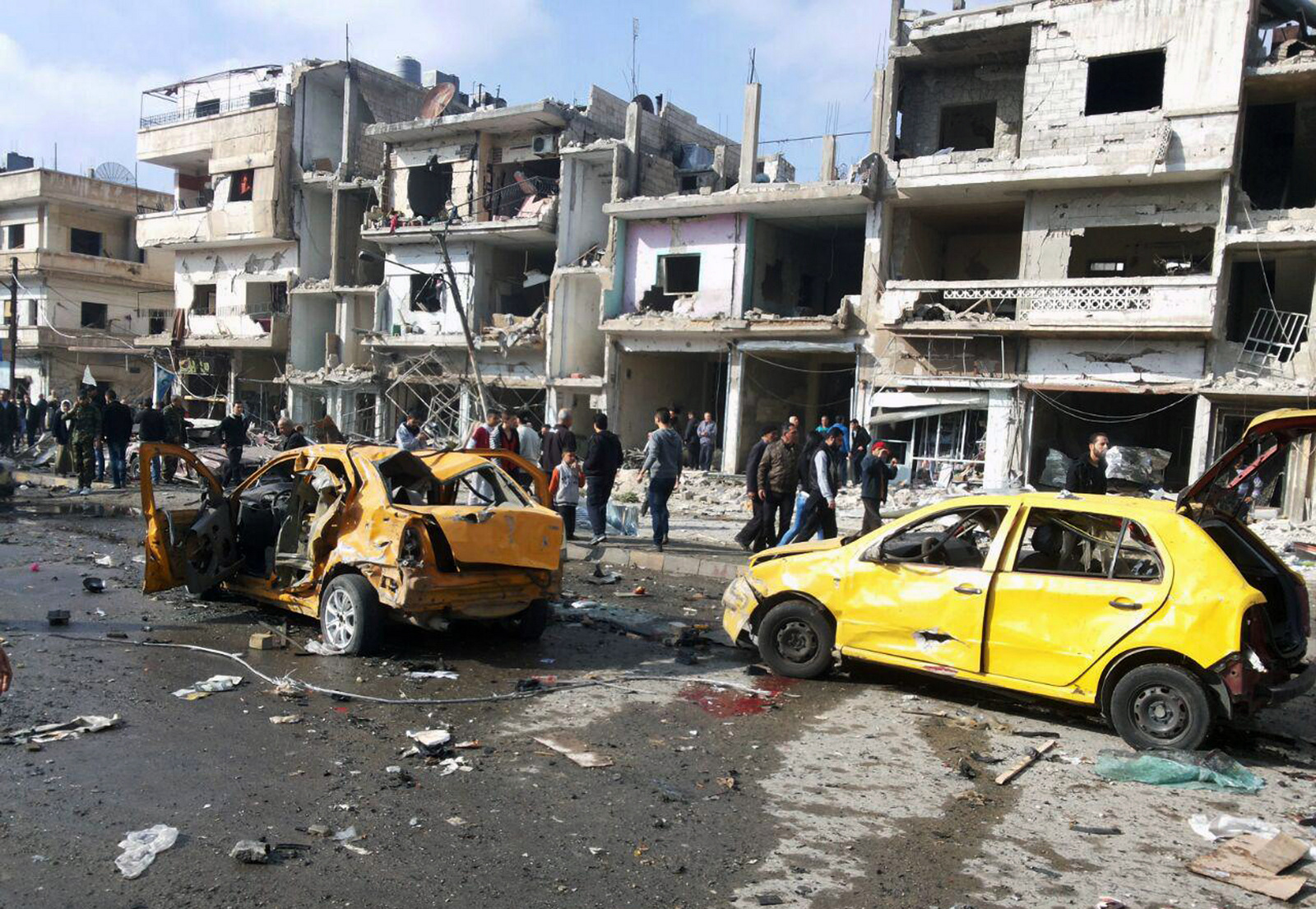 Syrian citizens gather at the scene where two blasts exploded in the pro-government neighborhood of Zahraa, in Homs province, Syria, Sunday, Feb. 21, 2016. Two blasts in the central Syrian city of Homs killed more than a dozen people and injured many others in a wave of violence. (SANA via AP)