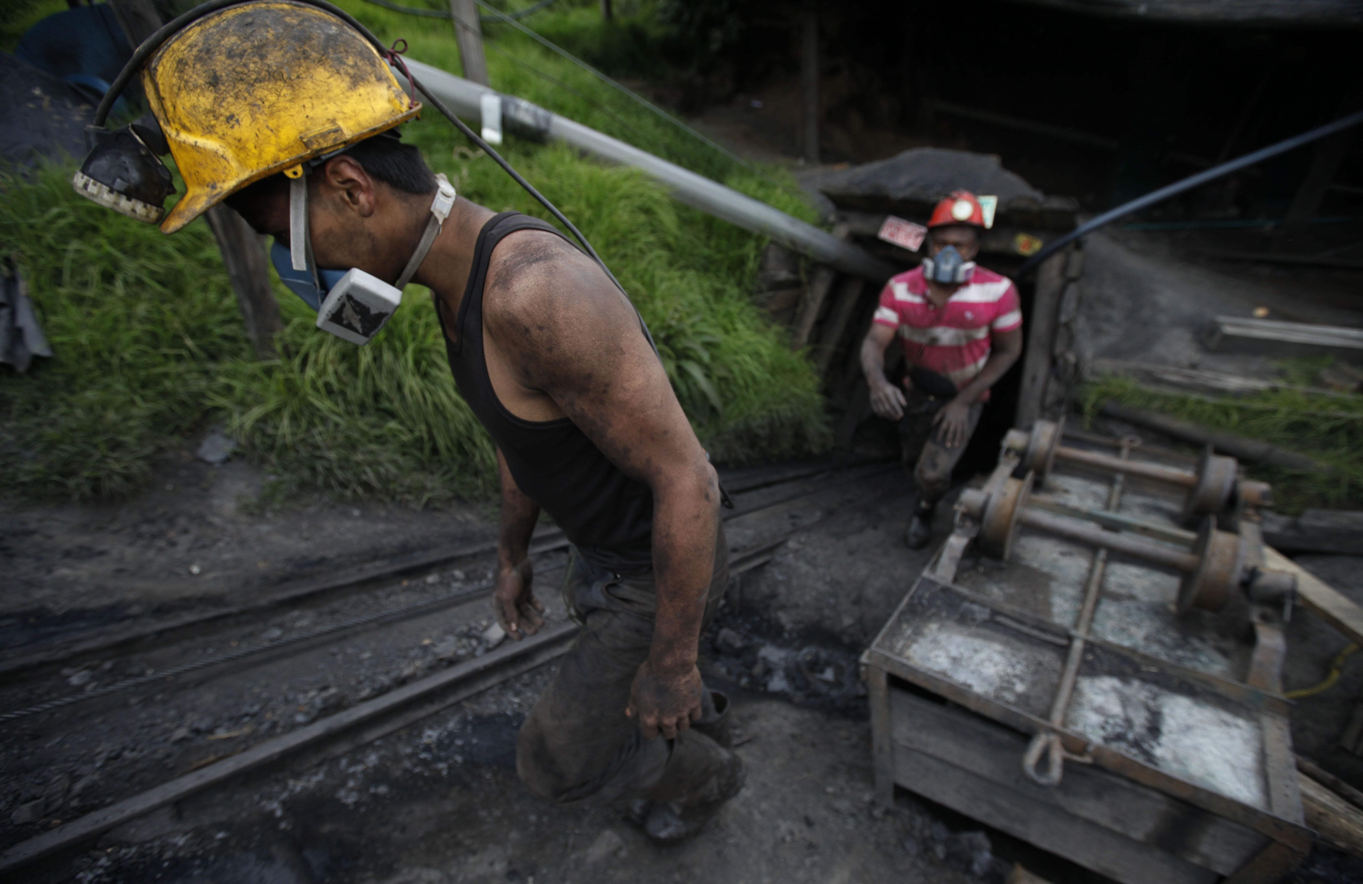 Miners leave the tunnel after their shift at La Flauta coal mine in Tausa, Colombia, Tuesday, Sept. 24, 2013. Tausa residents fear that La Flauta will be closed if authorities declare the area a nature reserve in which mining is prohibited. (AP Photo/Fernando Vergara)