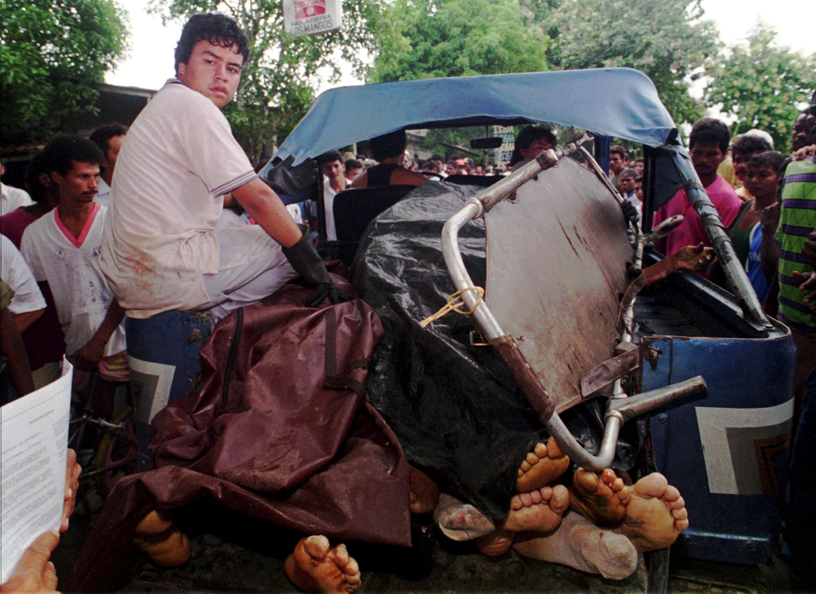 A man sits on the side of a jeep carrying the bodies of several of the at least 24 banana workers massacred by paramilitaries in the town of Apartado, Colombia, September, 1995. (AP Photo/Fernando Llano)