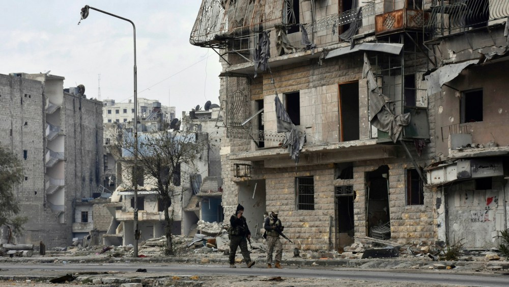 Syrian army soldiers march through the streets in the Ansari neighborhood, east Aleppo, Syria, Friday, Dec 23, 2016. (SANA via AP)