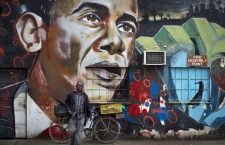 A man walks away after leaning his bicycle against a mural of President Barack Obama at the GoDown Arts Centre in Nairobi, Kenya ahead of the visit of Obama. (AP/Ben Curtis)