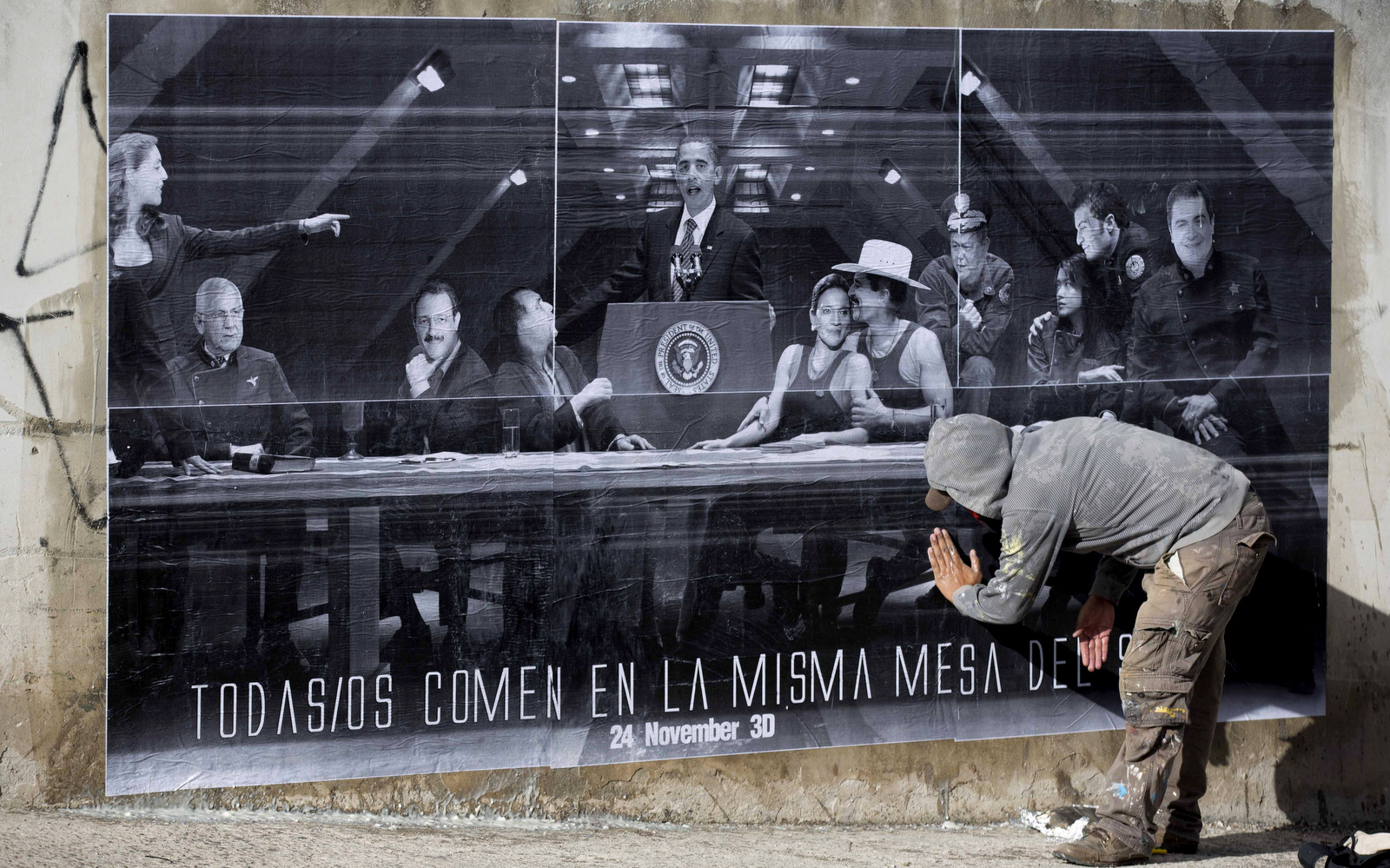 "An artist who prefers to remain anonymous for security reasons pastes up one of his ""interventions"" that shows President Barack Obama at a podium surrounded by Honduran politician in Tegucigalpa, Honduras, Thursday, Nov. 21, 2013. (AP/Eduardo Verdugo)"