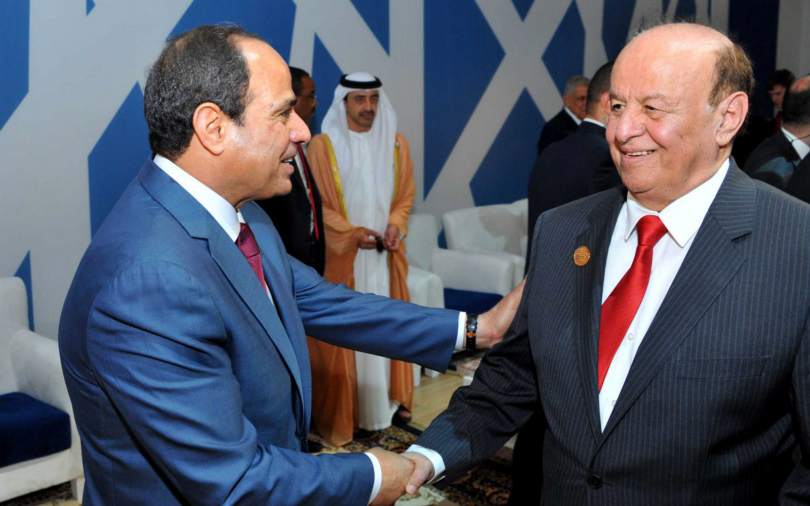 In this picture provided by the office of the Egyptian Presidency, Egyptian President Abdel-Fattah el-Sissi, left, talks to Yemen's exiled President Abed Rabbo Mansour Hadi following a ceremony unveiling a major extension of the Suez Canal in Ismailia, Egypt,, Aug. 6, 2015. (Egyptian Presidency via AP)