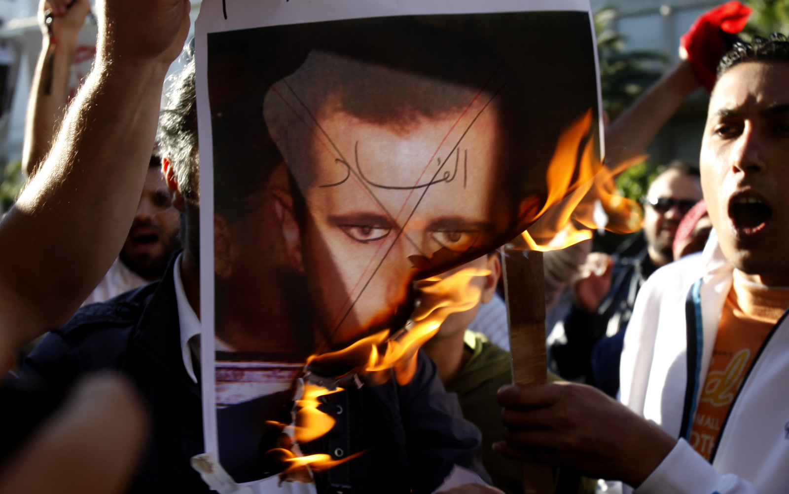 Anti-Assad protesters burn a picture of Syrian President Bashar al-Assad with 'Corruption' written across his face. (AP/Kostas Tsironis)