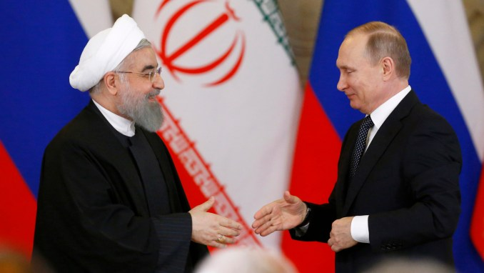 Russian President Vladimir Putin, right, shakes hands with Iranian President Hassan Rouhani during a joint news conference at the Kremlin in Moscow, Russia, Tuesday, March 28, 2017. Russia and Iran agreed to boost their energy cooperation and continue joint efforts to help Syrian settlement. (Sergei Karpukhin/AP)