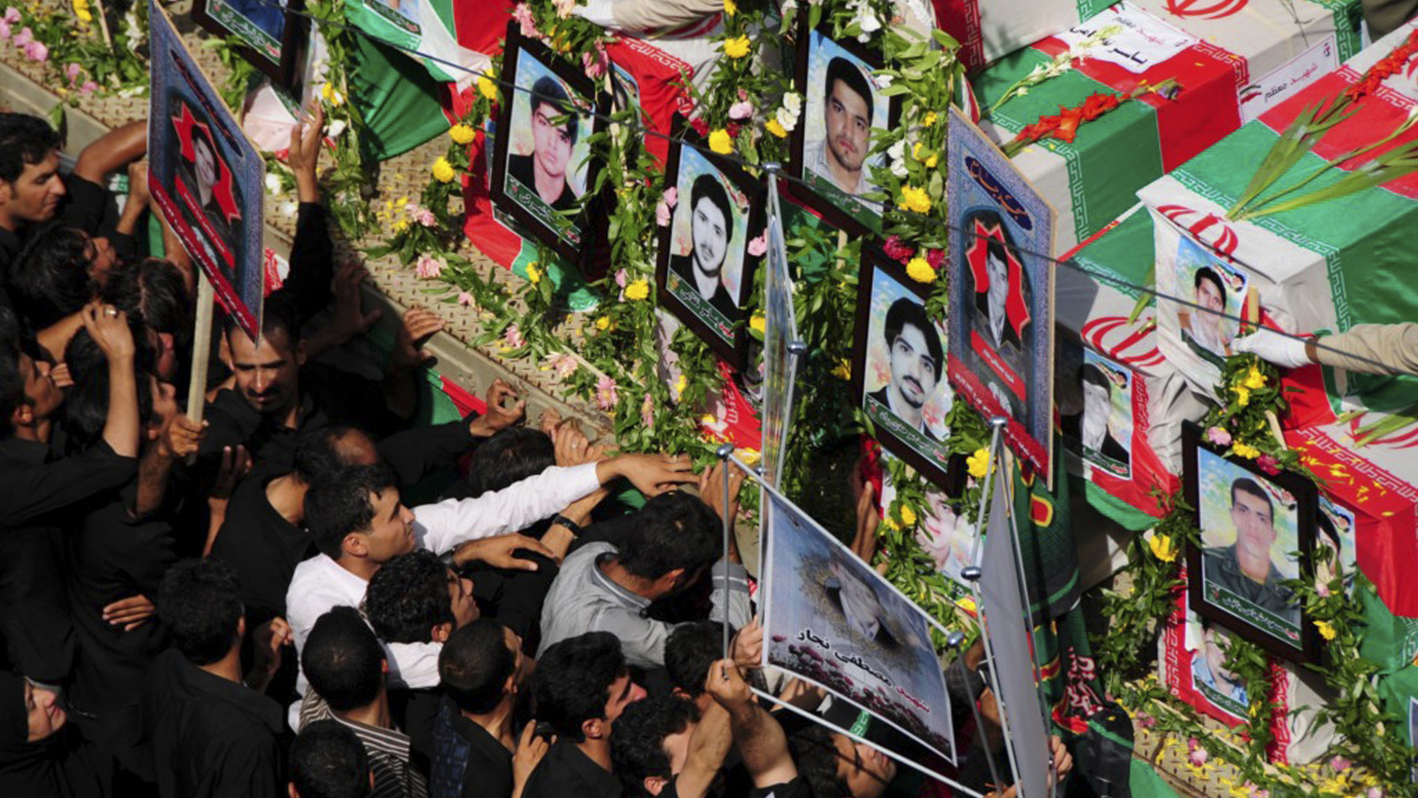 During a funeral ceremony, people mourn next to flag-draped coffins of victims of two bomb blasts in the city of Zahedan, Iran, July 17, 2010. Jundallah, which has carried out several other bombings in southeast Iran over the past few years, claimed responsibility for the blasts, which killed 27. (Fars/Ali Azimzadeh)
