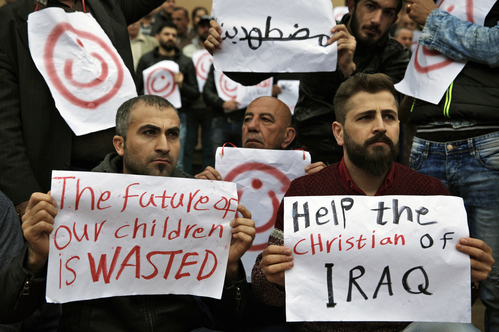 "Iraqi Christians who live in Lebanon hold placards during a sit-in, in front of the United Nations Headquarters demanding speeding up their immigration cases in Beirut, Lebanon, Feb. 13, 2017. Thousands of Christians from Iraq and Syria have fled violence in their country and sought refuge in Lebanon, a religiously-mixed country. The placard in Arabic reads ""Oppressed."" (AP/Bilal Hussein)"