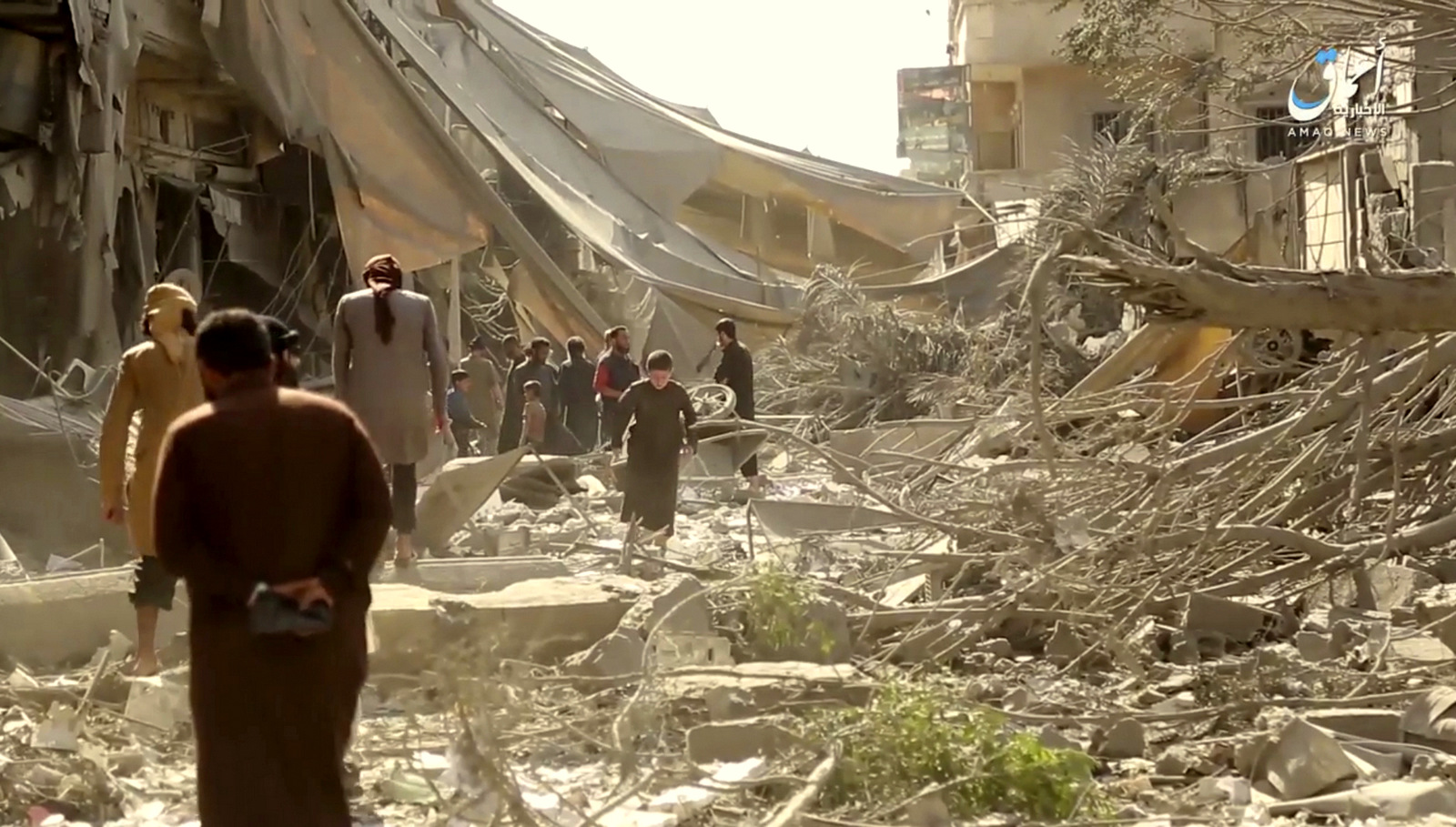People inspect damage from US coalition airstrikes and artillery shelling in the northern Syrian city of Raqqa, Syria, May 29, 2017. (Aamaq via AP)