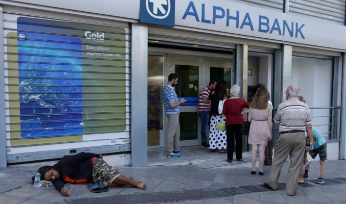 People queue in front of a bank for an ATM as a man lies on the ground begging for change, in Athens. (AP/Thanassis Stavrakis)