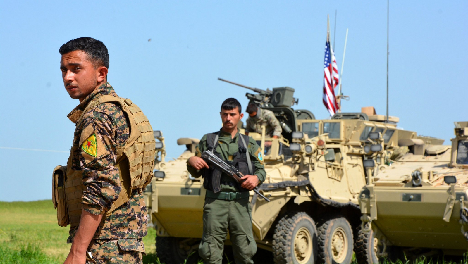 Kurdish fighters from the People's Protection Units, (Y.P.G), stand guard next to American armored vehicles at the Syria-Turkey border, Apri, 2017. (Youssef Rabie Youssef/EPA)