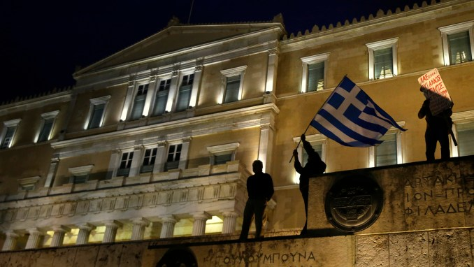 A man waves a Greek flag in front of the Greek Parliament during a rally against new austerity measures in Athens, May 18, 2017. (AP/Yorgos Karahalis)