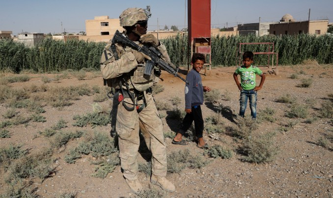 A U.S. soldier stands near Syrian children on a road that links to Raqqa, Syria, July 26, 2017. The U.S. has at least 1,000 troops in Syria. (AP/Hussein Malla)