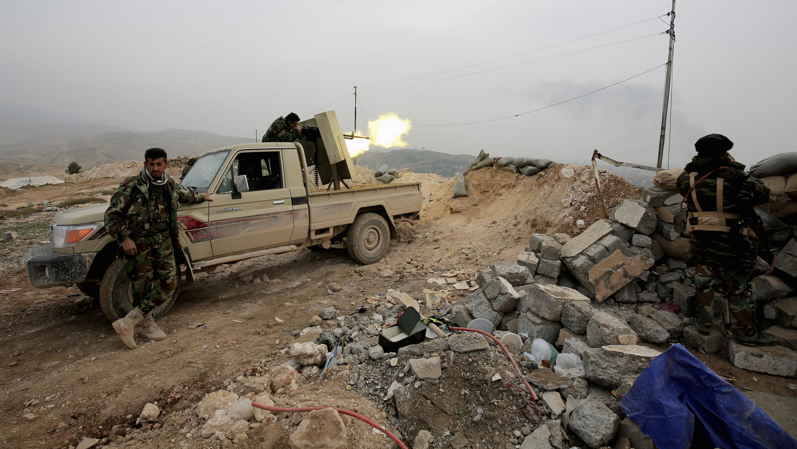 Well-armed Kurdish Peshmerga fighters fire a weapon toward the strategic town of Sinjar, northern Iraq. . (AP/Bram Janssen)