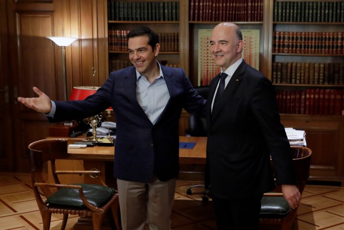 Greek Prime Minister Alexis Tsipras, left, welcomes European Commissioner for Economy Pierre Moscovici at Maximos Mansion in Athens, July 25, 2017. Greece is poised to tap international bond markets for the first time in three years in a move the government claims will signal the country is ready to emerge from its bailout era. (AP/Thanassis Stavrakis)