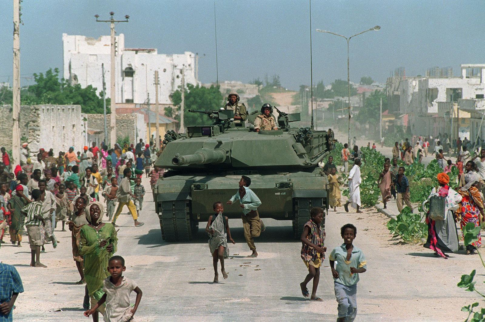 Somali children run alongside a U.S. Marine M-1 Abrams tank during an armored patrol in north Mogadishu, Somalia, Jan. 26, 1993. (AP/Mark Duncan)