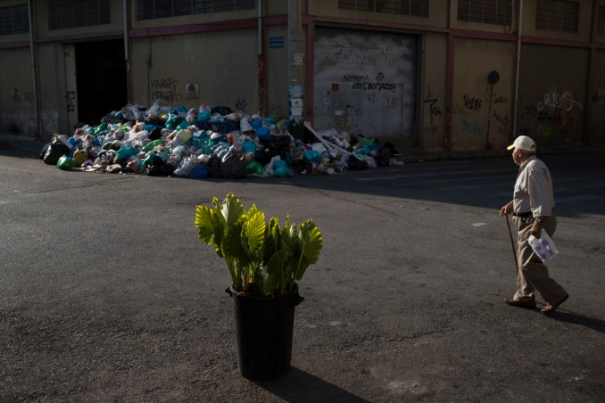 A man looks on a pile of trash as he walks behind a flower pot in Kaminia neighborhood of Piraeus, near Athens, June 27, 2017. Striking garbage collectors who fear job losses from EU-imposed regulations governing short-term contract workers in the public sector, were on the 11th-day of protest that left huge piles of trash around Athens. (AP/Petros Giannakouris)